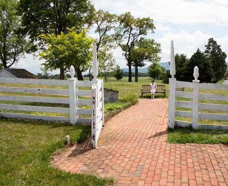 Senior woman sitting on bench on brick path through white picket gate photo