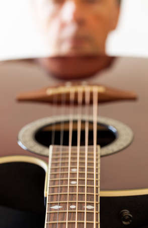 acoustical: Macro shot down the fretboard of acoustic guitar with shallow depth of field with guitarist face in the distance reflected