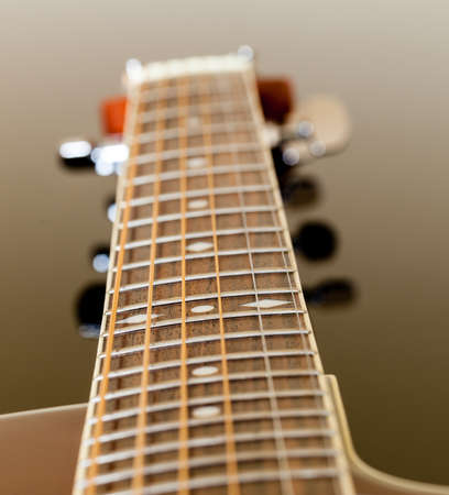 fretboard: Macro shot down the fretboard of acoustic guitar with shallow depth of field