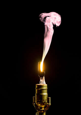 Filament on broken incandescent light bulb flares and gives off smoke photo