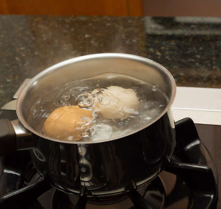 Two eggs in boiling water in stainless steel pan on gas hob photo