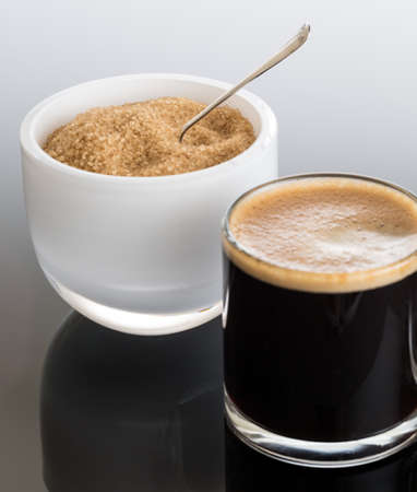 sweeten: Black expresso coffee in small glass cup with sugar in white bowl reflecting Stock Photo