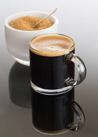 Black expresso coffee in small glass cup with sugar in white bowl reflecting Stock fotó