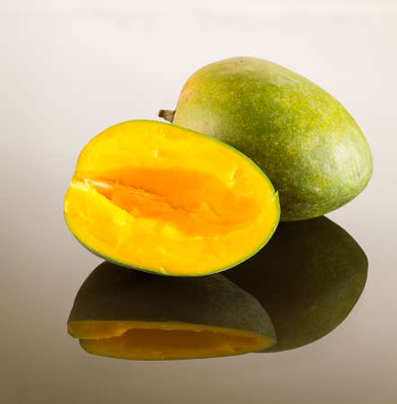 two and a half: One whole and one cut mango on reflecting glass surface with gradient Stock Photo