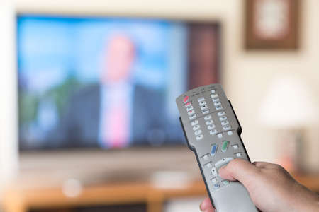 watch video: Silver modern TV remote control being pressed by thumb with out of focus screen background
