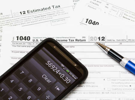 Tax form 1040 for tax year 2012 for US individual tax return with smartphone calculator photo