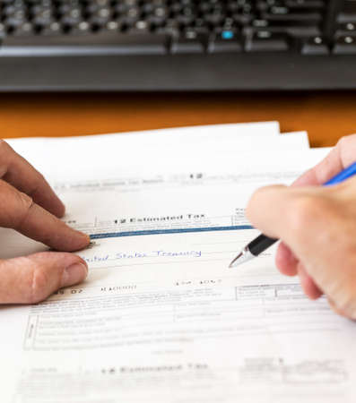 Tax form 1040 for tax year 2012 for US individual tax return with pen and check
