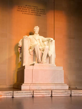 Rising sunrise at dawn lights statue of President Lincoln in memorial in Washington DC photo