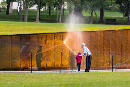 WASHINGTON DC - SEPTEMBER 16: Volunteers clean Vietnam Memorial wall on September 16, 2012. The Wall was completed by Maya Lin in 1982.