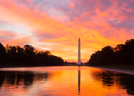 monument: Bright red and orange sunrise at dawn reflects Washington Monument in new reflecting pool by Lincoln Memorial Stock Photo