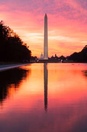 Zářivě červené a oranžové slunce za úsvitu odráží Washington památník v novém odrážející bazénu o Lincolnův památník