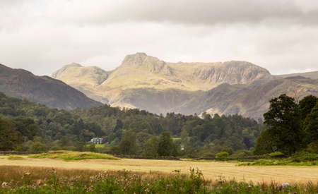 Sun illuminating Langdale Pikes in English Lake District Stock Photo - 15363452