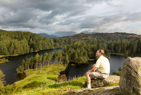 lake district: Senior hiker looks over Tarn Hows in English Lake District