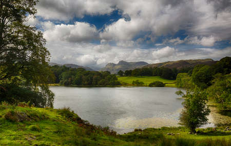 Sun illuminating Langdale Pikes with Loughrigg Tarn in foreground photo