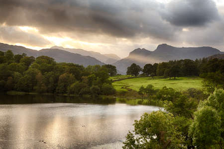Sun setting over Langdale Pikes with Loughrigg Tarn in foreground