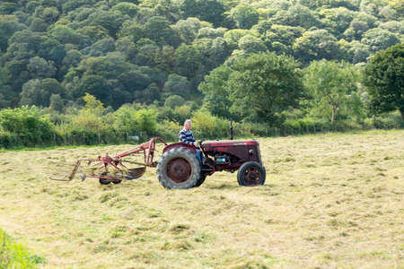 BUTTERMERE, ENGLAND - SEPTEMBER 5: Farmer threshing corn using antique tractor on 5 September 5, 2012.