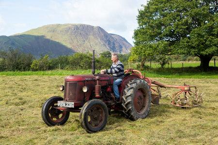 thresh: BUTTERMERE, ENGLAND - SEPTEMBER 5: Farmer threshing corn using antique tractor on September 5, 2012. Editorial