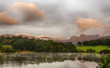 langdale pikes: Sun rising and illuminating Langdale Pikes with Loughrigg Tarn in foreground