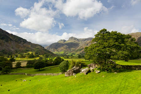 Sun illuminating Langdale Pikes in English Lake District