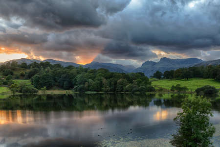 Sun setting over Langdale Pikes with Loughrigg Tarn in foreground Stock Photo - 15363468