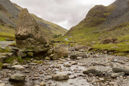 cumbria: Rocky stream runs by steep road in Honister Pass in English Lake District