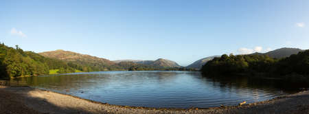 Panorama of Grasmere in Lake District as sunrise as sun light mountains Stock Photo