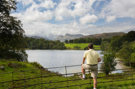 Sun illuminating Langdale Pikes with Loughrigg Tarn in foreground and hiker photo