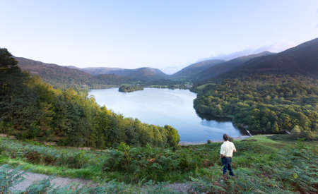 Senior man overlooks Grasmere in Lake District as sunrise as sun light mountains photo