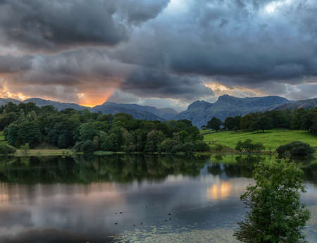 Sun setting over Langdale Pikes with Loughrigg Tarn in foreground Stock Photo - 15363463