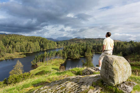 cumbria: Senior hiker looks over Tarn Hows in English Lake District