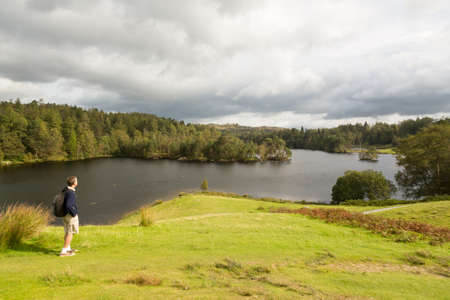 Senior hiker looks over Tarn Hows in English Lake District Stock Photo - 15369719
