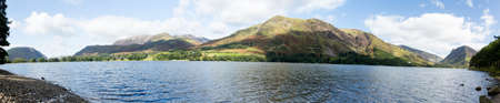 Mountains reflect into Buttermere calm lake in English Lake District photo