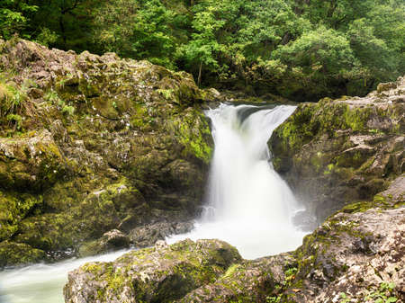 cumbria: Skelwith Falls waterfall with green moss in slow motion shot in Lake District Stock Photo