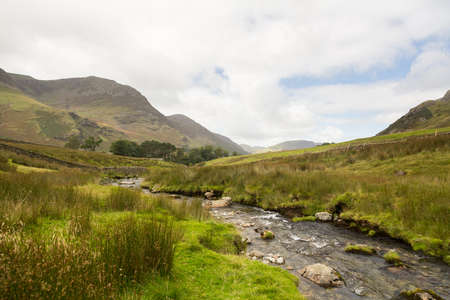 cumbria: Rocky river leads to Buttermere over Honister Pass in English lake District