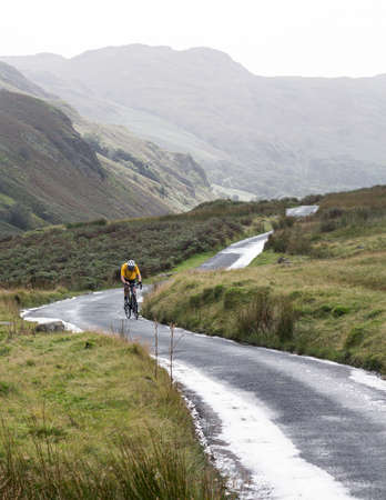 cumbria: Cyclist on steep hairpin bends on Handknott pass in English Lake District