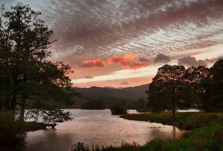 cumbria: Setting sun illuminates clouds over Rydal Water in English Lake District