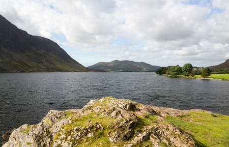 View of Crummock Water past trees and island in English Lake District Stock Photo - 15363372