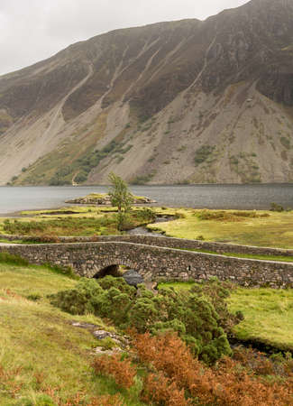 Ancient stone bridge over river running into Wastwater in Lake District photo