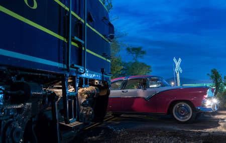 Blue train diesel railway engine almost hits vintage thunderbird car at railroad crossing at night
