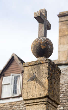 sun dial: Old sun dial topped with orb and cross in Cotswolds town of Stanton