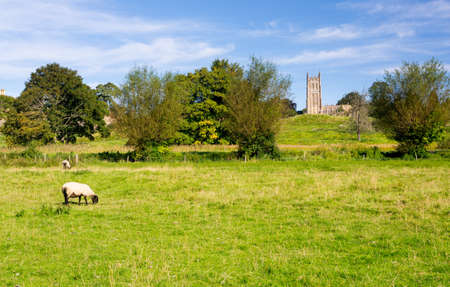 british weather: St James Church seen across meadow with sheep in old Cotswold town of Chipping Campden
