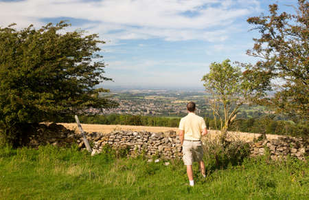 Senior man looks at views over Winchcombe from the barrow at Belas Nap in English Cotswolds photo