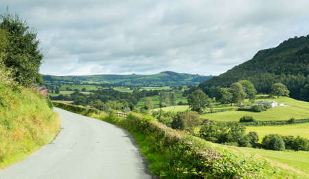 british weather: North Wales valley and farmland with country road leading to distance