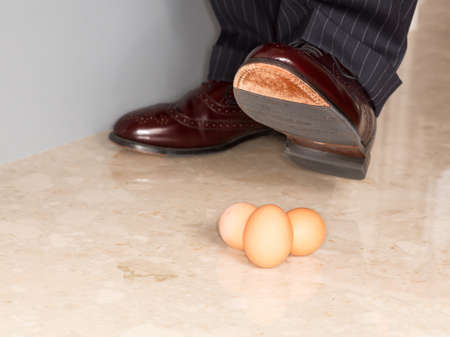 Male brown leather shoe in suit pants about to tread on three brown eggs photo