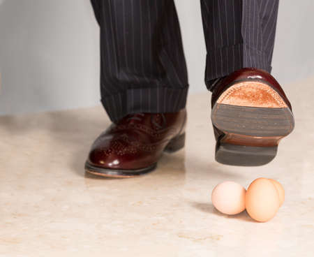 under pressure: Male brown leather shoe in suit pants about to tread on three brown eggs Stock Photo