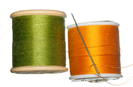 objects: Green and Orange cotton thread on bobbins isolated against white