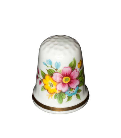 thimble: White china thimble with flowers painted isolated against white