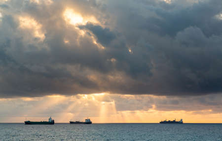 Three cargo or freight ships on horizon at sunset on cloudy stormy evening photo