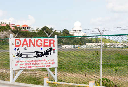 approached: PRINCESS JULIANA AIRPORT, ST MARTIN -  NOVEMBER 1: Warning sign by Maho beach about low planes on November 1, 2012. The 2300m runway is approached over the sea.