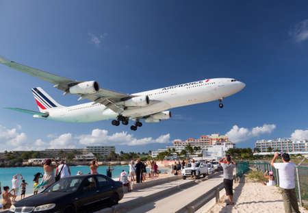 PRINCESS JULIANA AIRPORT, ST MARTIN -  NOVEMBER 1: Air France flight lands over Maho beach on November 1, 2012. The 2300m runway is approached over the sea.